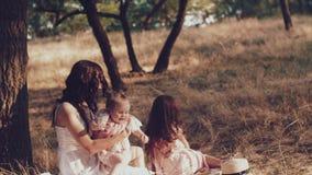 Una giovane madre e due figlie riposano su un picnic archivi video
