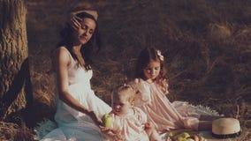 Una giovane madre e due figlie riposano su un picnic stock footage