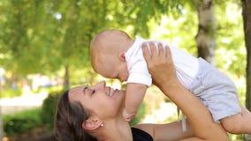 Una giovane madre felice cammina con un neonato nel tempo caldo nel parco stock footage