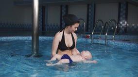 Una giovane madre insegna al suo piccolo figlio a nuotare nello stagno Addestramento di nuoto archivi video