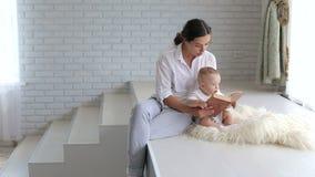 Una giovane madre legge un libro al suo bambino neonato in un appartamento moderno video d archivio