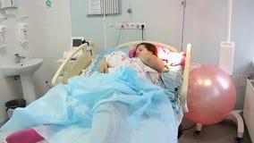 Una giovane madre si trova con un neonato nel reparto di maternità Rilassi dopo il parto archivi video