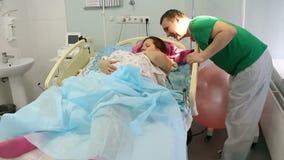 Una giovane madre si trova con un neonato nel reparto di maternità Rilassi dopo il parto Il padre felice la bacia video d archivio