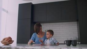 Una giovane madre spagnola con suo figlio che si siede alla tavola insegna a per leggere il bambino che aiuta e che richiama suo  stock footage