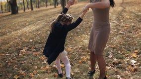 Una giovane madre sta filando sua figlia intorno a se stessa in un parco della città di autunno Una famiglia felice stock footage