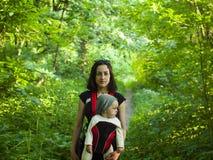 Una giovane madre in vestito orientale, tenente un piccolo bambino in un bambino immagini stock libere da diritti
