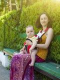 Una giovane madre in vestito orientale, tenente un piccolo bambino in un bambino fotografia stock