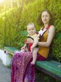 Una giovane madre in vestito orientale, tenente un piccolo bambino in un bambino fotografie stock libere da diritti