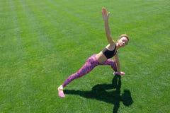 Una giovane ragazza afroamericana in una maglietta nera, nei pantaloni rosa e nelle scarpe da tennis facenti gli sport si esercit immagine stock libera da diritti