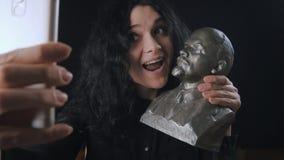 Una giovane ragazza allegra fa un selfie con un busto di Lenin video d archivio