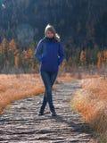 Una giovane ragazza atletica sta stando su un percorso di legno sopra l'acqua nella stagione gelida di autunno fotografie stock