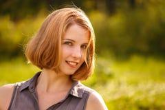 Una giovane ragazza bionda che sorride felicemente nei raggi del sole luminoso su fondo verde Fotografia Stock
