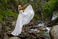 Una giovane ragazza bionda in una posa elegante getta sul bordo di un vestito dal boudoir nelle montagne contro un innalzamento d fotografie stock
