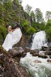 Una giovane ragazza bionda in una posa elegante getta sul bordo di un vestito dal boudoir nelle montagne contro un innalzamento d immagini stock