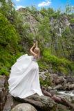 Una giovane ragazza bionda in una posa elegante tira su un boudoir per agghindarsi nelle montagne contro una cascata e le pietre  fotografia stock libera da diritti