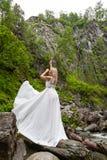 Una giovane ragazza bionda in una posa elegante tira su un boudoir per agghindarsi nelle montagne contro una cascata e le pietre  fotografie stock