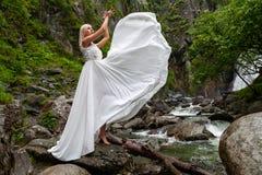Una giovane ragazza bionda in una posa elegante tira su un vestito dal boudoir nelle montagne contro una cascata e le pietre che  fotografie stock libere da diritti