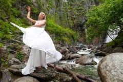 Una giovane ragazza bionda in una posa elegante tira su un vestito dal boudoir nelle montagne contro una cascata e le pietre che  fotografia stock libera da diritti