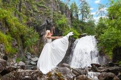 Una giovane ragazza bionda in una posa elegante tira su un vestito dal boudoir nelle montagne contro una cascata e le pietre che  fotografie stock