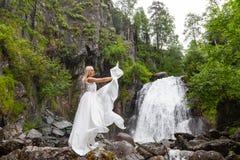 Una giovane ragazza bionda in una posa elegante tira su un vestito dal boudoir nelle montagne contro una cascata e le pietre che  immagini stock
