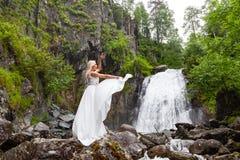 Una giovane ragazza bionda in una posa elegante tira su un vestito dal boudoir nelle montagne contro una cascata e le pietre che  immagine stock libera da diritti