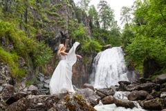Una giovane ragazza bionda in una posa elegante tira su un vestito dal boudoir nelle montagne contro una cascata e le pietre che  immagine stock