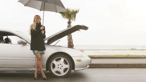 Una giovane ragazza bionda sta accanto alla sua automobile rotta sotto l'ombrello archivi video