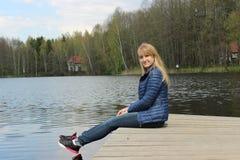Una giovane ragazza bionda sta sedendosi sulla riva del lago Fotografia Stock Libera da Diritti