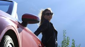 Una giovane ragazza castana alla moda in bomber ed occhiali da sole sta stando accanto ad un convertibile rosso archivi video