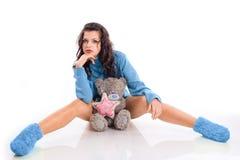 Una giovane ragazza castana con il suo orsacchiotto Immagine Stock