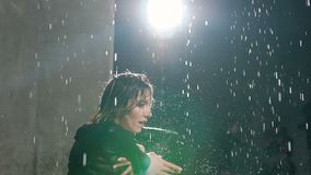 Una giovane ragazza caucasica esegue a piedi nudi una danza moderna nell'acqua al di sotto delle gocce di pioggia allo studio Bal stock footage