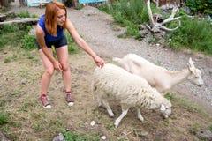 Una giovane ragazza dai capelli rossi in un cappuccio bianco, negli shorts blu del denim ed in una a fotografia stock libera da diritti