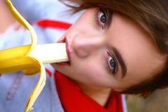 Una giovane ragazza dolce è molto seducente mangiando una banana Una donna di sport guarda il suo alimento fotografie stock