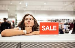 Una giovane ragazza esile amichevole con capelli lunghi, attrezzatura casuale d'uso, sta facendo la spesa in un centro commercial fotografie stock
