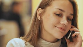 Una giovane ragazza graziosa legge e scrive i messaggi sul telefono che si siede in un caffè alla tavola Primo piano Fotografie Stock Libere da Diritti