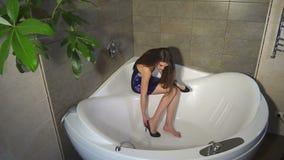 Una giovane ragazza sexy in un vestito si siede in un bagno vuoto con le scarpe in sue mani stock footage