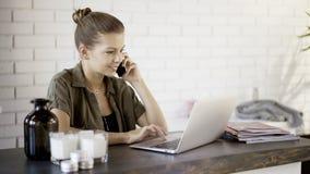 Una giovane ragazza sorridente sta avendo una chiamata che wotking con un computer portatile Fotografia Stock Libera da Diritti