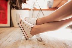 Una giovane ragazza sveglia, attrezzatura casuale d'uso, sta sedendosi con le sue gambe ha attraversato in una caffetteria accogl fotografie stock libere da diritti