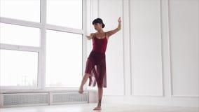 Una giovane signora balla, una donna elegante realizza i movimenti della danza moderna stock footage