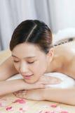 Una giovane signora che gode del massaggio di pietra alla stazione termale Fotografia Stock