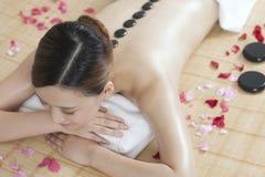 Una giovane signora che gode del massaggio di pietra alla stazione termale Immagine Stock Libera da Diritti