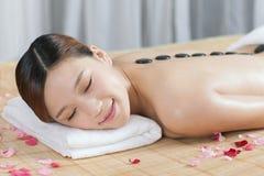Una giovane signora che gode del massaggio di pietra alla stazione termale Fotografie Stock