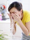 Una giovane signora che lava il suo fronte immagini stock