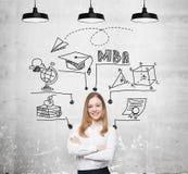 Una giovane signora sorridente sta pensando al grado di MBA Il grafico educativo è tracciato dietro lei Un concetto di più univer fotografia stock libera da diritti
