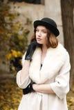 Una giovane signora in un black hat e guanti e un cappotto leggero sta e guarda esteriormente retro all'aperto fotografia stock