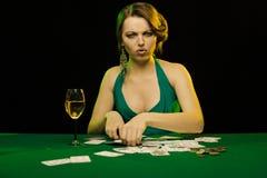 Una giovane signora in un vestito verde fuma una sigaretta e soffia il fumo e gioca le carte fotografia stock libera da diritti