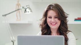 Una giovane signora Using un computer all'interno fotografie stock