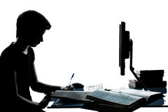 Una giovane siluetta della ragazza del ragazzo dell'adolescente che studia con il computer c Fotografia Stock