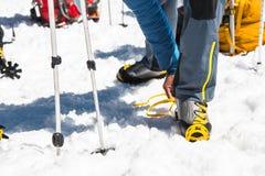 Una giovane viandante del tipo veste i ramponi rampicanti sopra le scarpe di alpinismo per la camminata attraverso il ghiacciaio Fotografia Stock Libera da Diritti