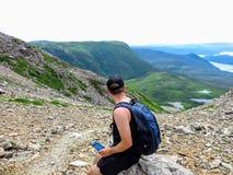 Una giovane viandante maschio che ammira le viste spettacolari in cima a Gros Morne Mountain a Gros Morne National Park fotografia stock libera da diritti